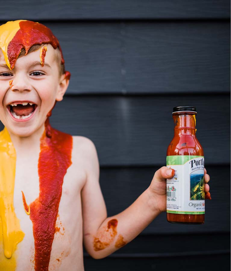 Little boy with a big smile on his face holding a bottle of Portland Organic Mustard and Portland Organic Ketchup. The ketchup and mustard have been poured on his head and is dripping down, the boy is happy and content