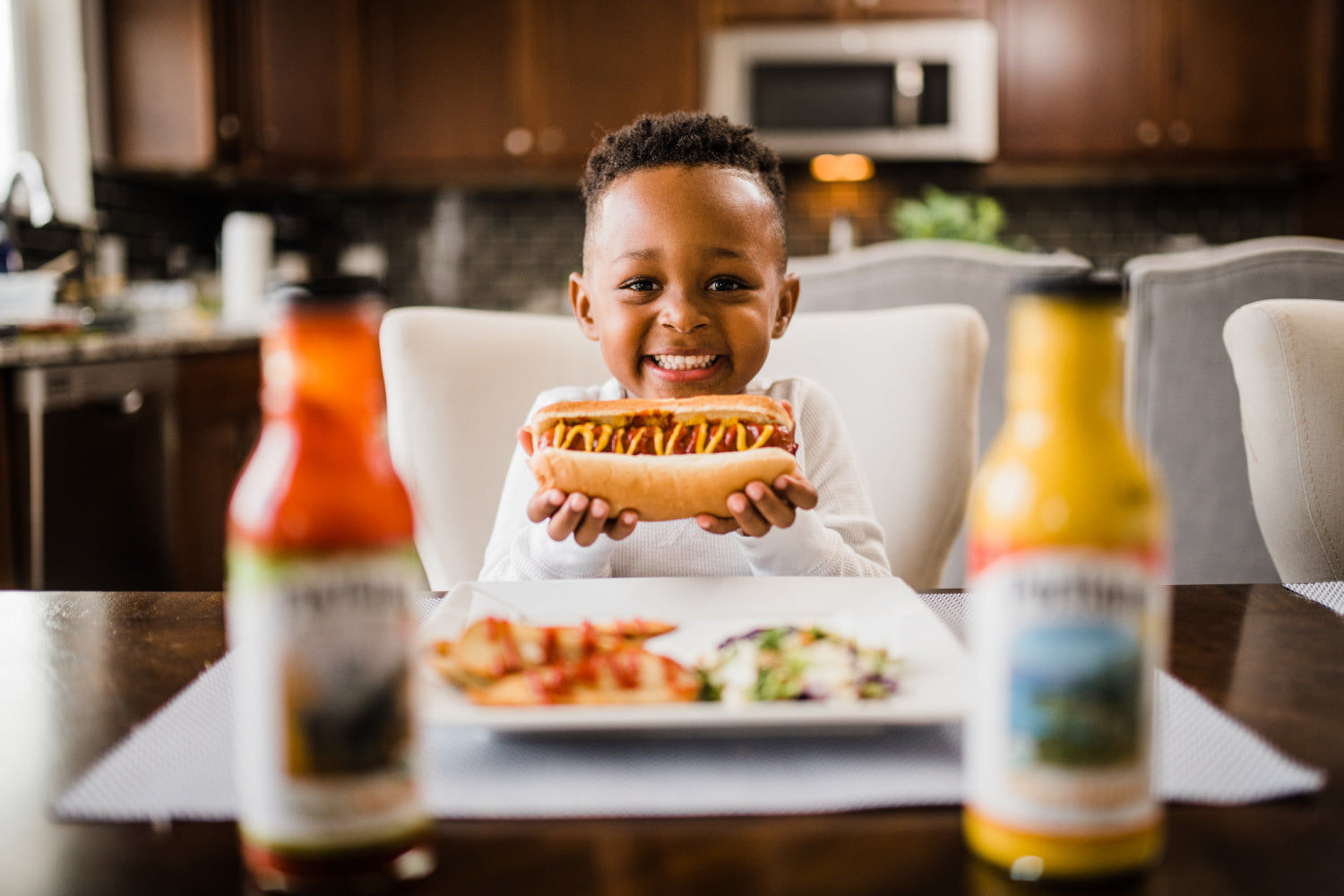 Cute boy of color holding a hotdog with a big smile and Portland Organic Ketchup and Portland Organic Mustard in the foreground