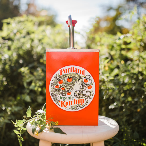 Portland Organic Ketchup Stainless Steel Pump 1 gallon dispenser with Portland Organic Ketchup Label on the front, sitting in a garden
