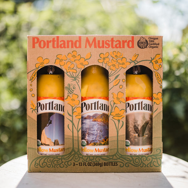 Portland Organic Mustard 3-Bottle Gift Pack sitting on a table outside, no GMOs, Gluten Free, Dairy Free