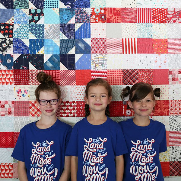 Three girls wearing by This Land Was Made for You and Me t-shirts by Stately Type in front of a USA flag quilt made from the Yankee Doodle Dandy quilt pattern by Maker Valley