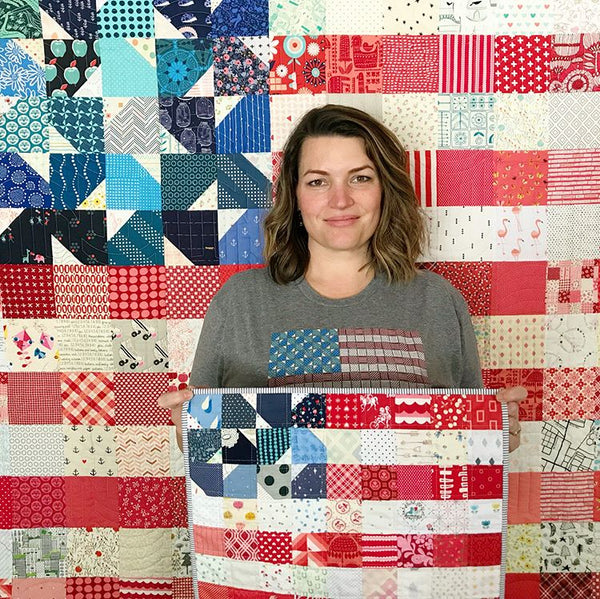Holly Lesue wearing a Yankee Doodle Dandy Quilt USA Flag t-shirt by Maker Valley holding a USA flag mini quilt in front of a USA flag quilt made from the Yankee Doodle Dandy quilt pattern by Maker Valley