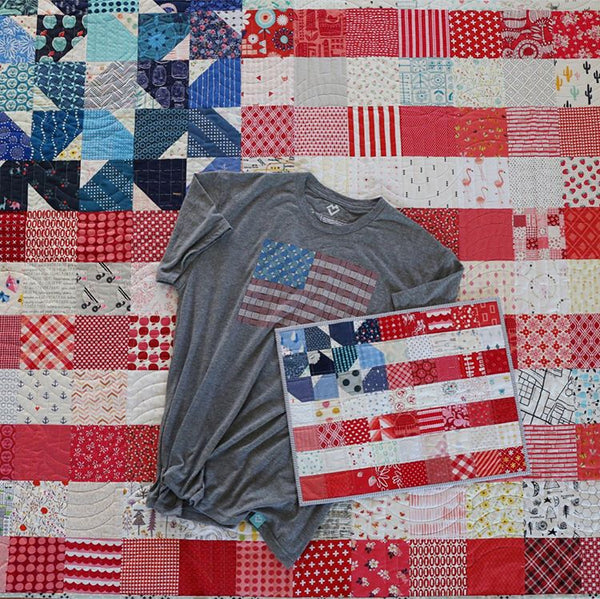 A Yankee Doodle Dandy Quilt USA Flag t-shirt by Maker Valley and a american flag mini quilt in front of a USA flag quilt made from the Yankee Doodle Dandy quilt pattern by Maker Valley