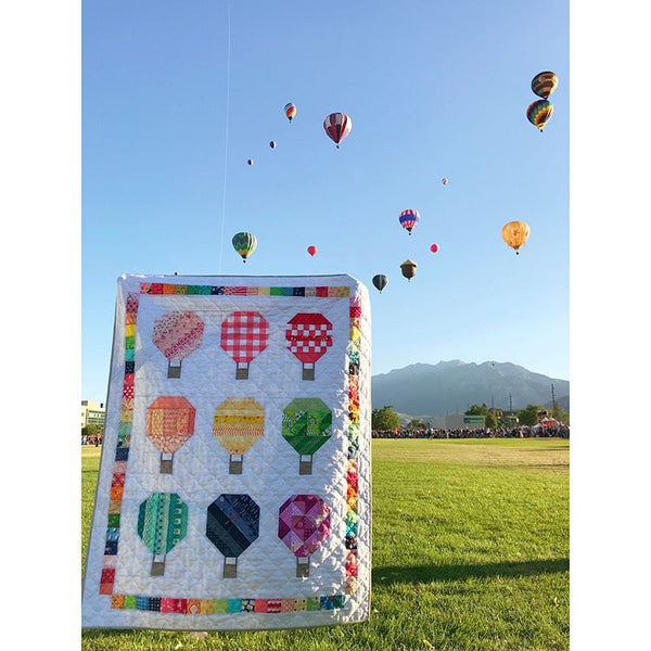 A hot air balloon-themed quilt made from the Rise quilt pattern by Woodberry Way in front off the hot air balloons at the Freedom Festival in Provo, Utah
