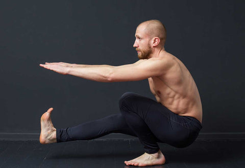 man performing a pistol squat - single-legged squat