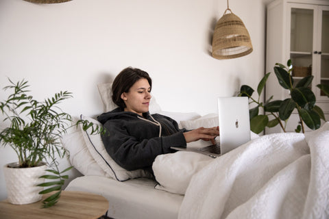 woman lying in bed enjoying an online course