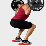 Weight lifter using squat wedges to better his technique during back squat
