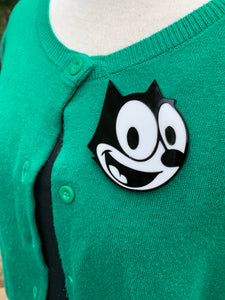felix the cat brooch on a green cardigan