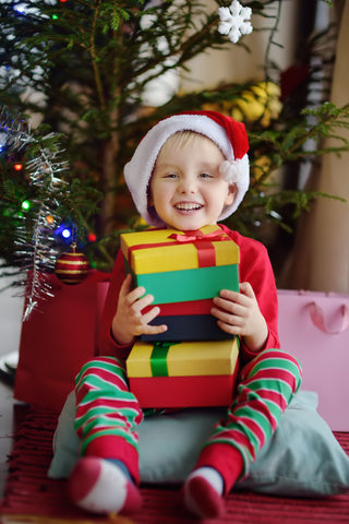 cute boy with a stack of presents