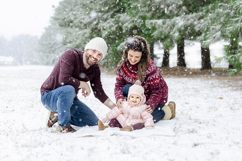 family posing in the snow for a christmas photo