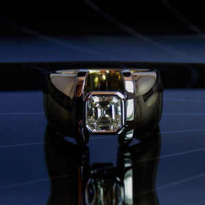 Wide white and yellow gold dress ring with emerald cut diamond