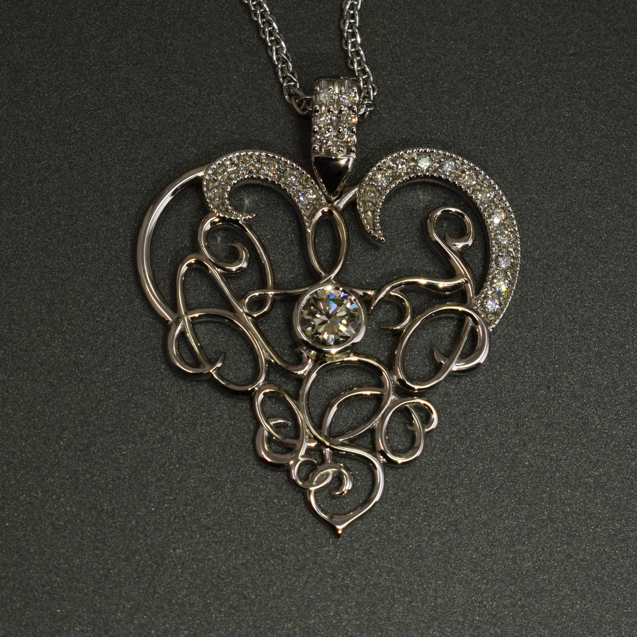 Calligraphy heart shaped pendant with diamonds in white gold