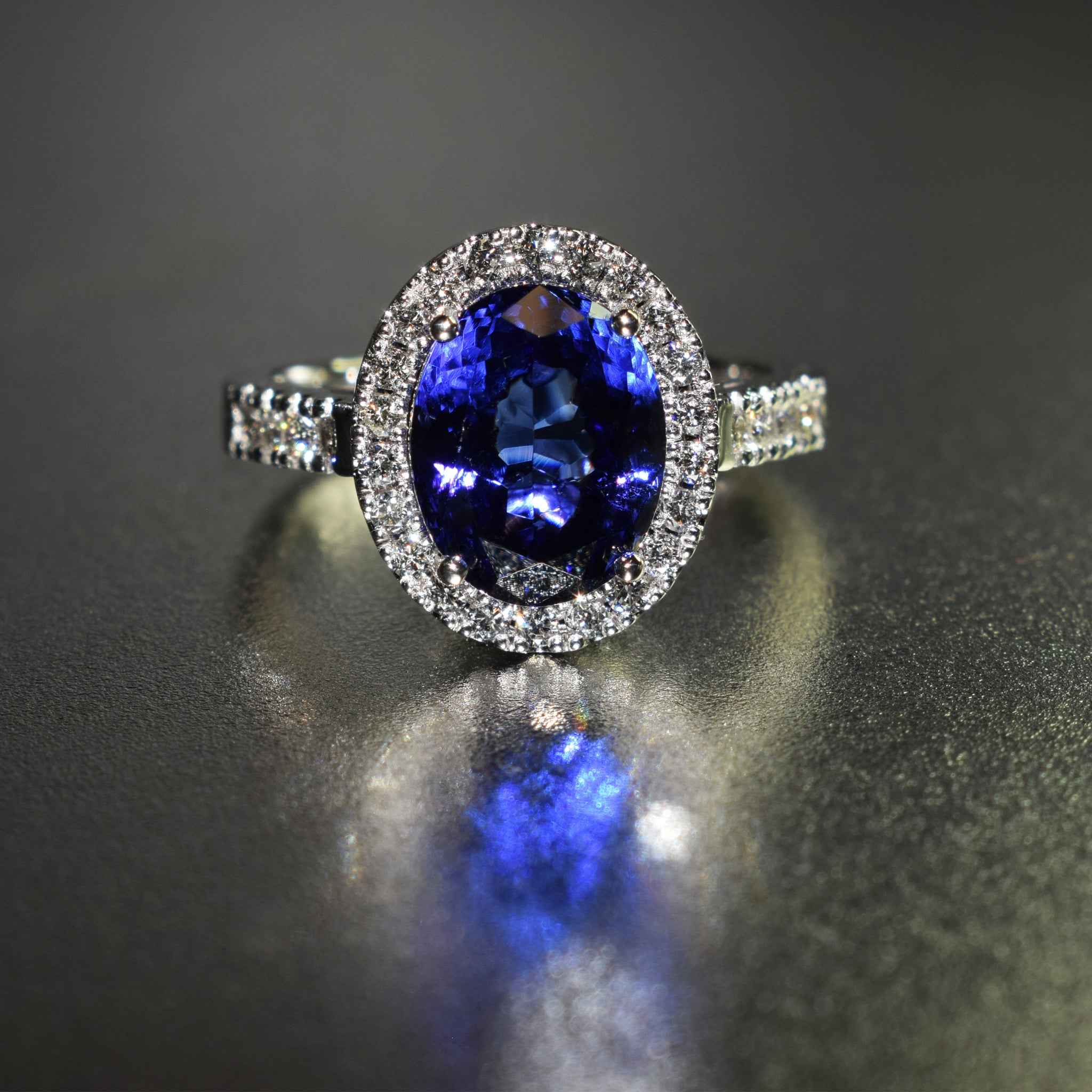 Oval tanzanite with diamond halo in 18K white gold