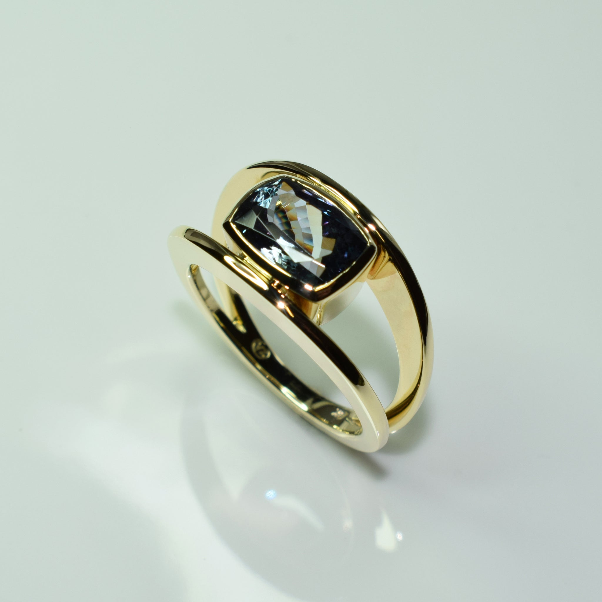 Yellow gold split band ring with cushion cut tanzanite