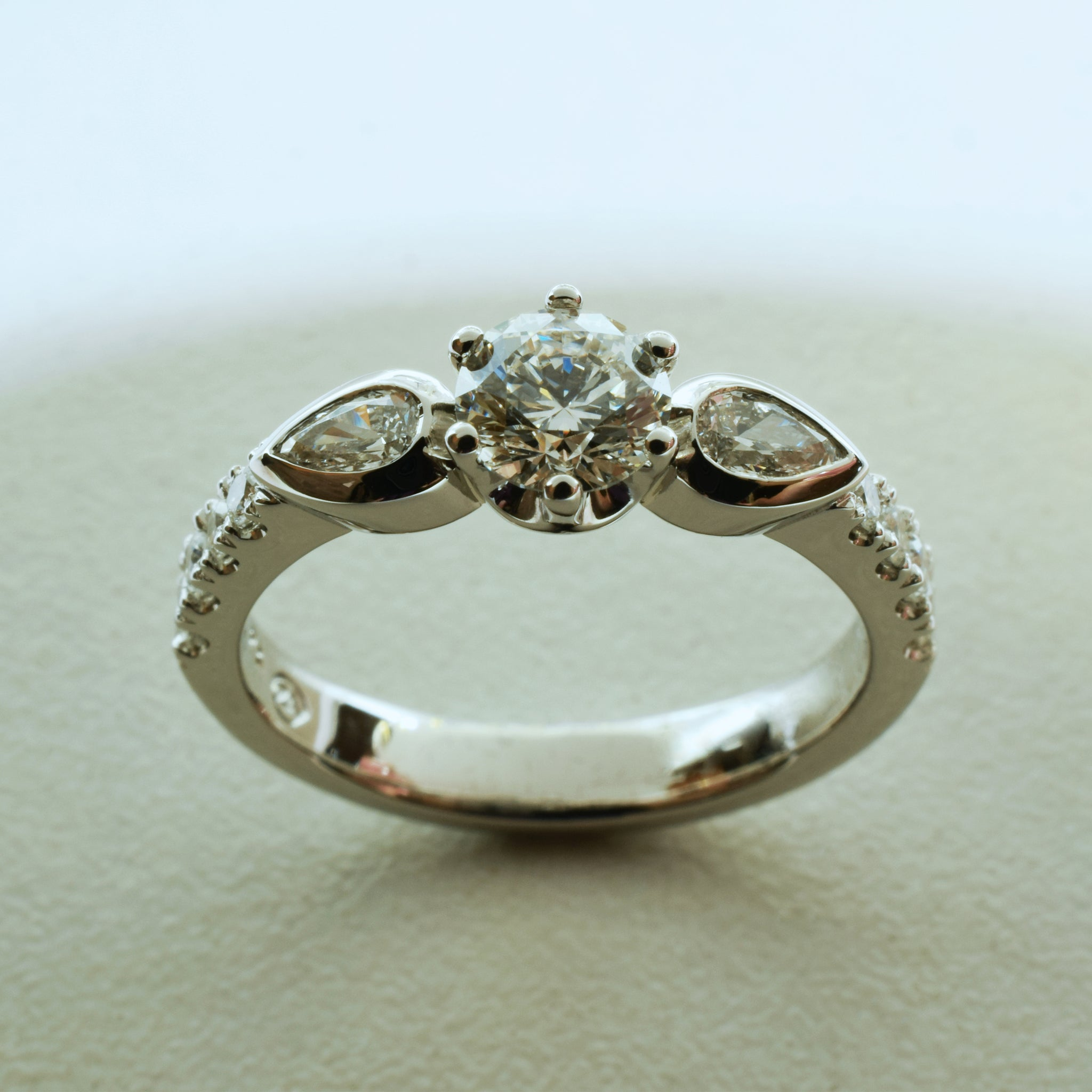 Round brilliant and pear diamond trilogy ring set in platinum