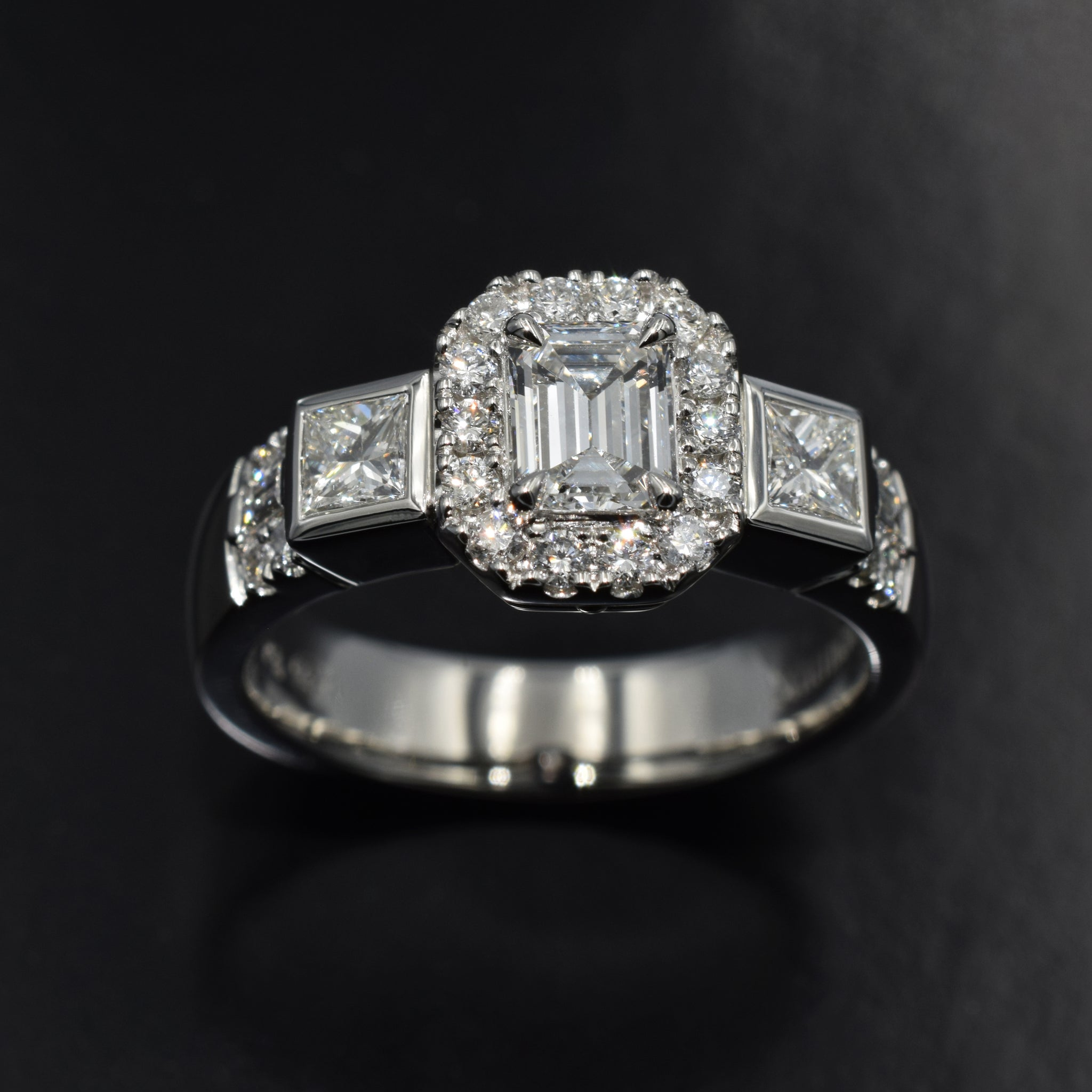 Platinum halo trilogy ring with emerald cut diamond center and princess cut sides