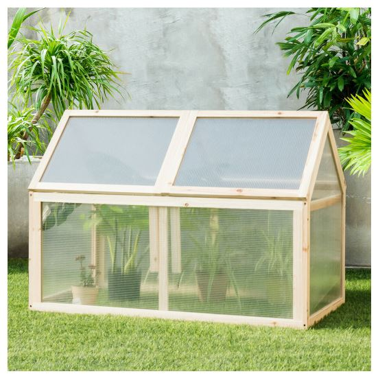Cold frame greenhouse sitting on lawn between trees