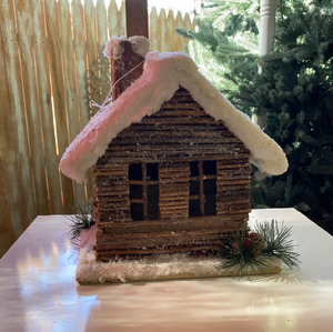Wood house w/snow covered roof and greenery