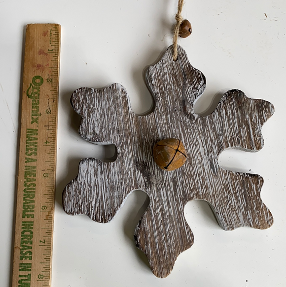 Brown and white wooden holiday snowflake with jingle bell in middle