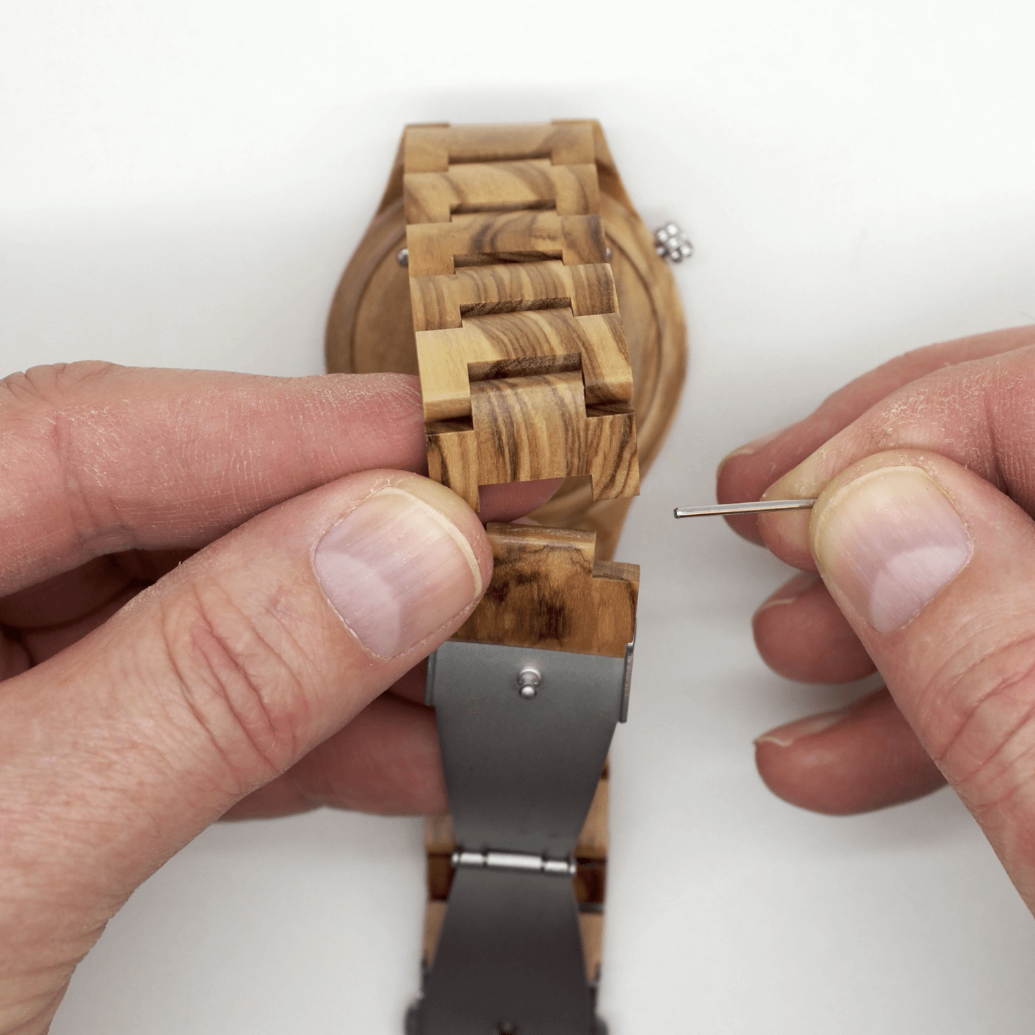 Person separating wooden watch links