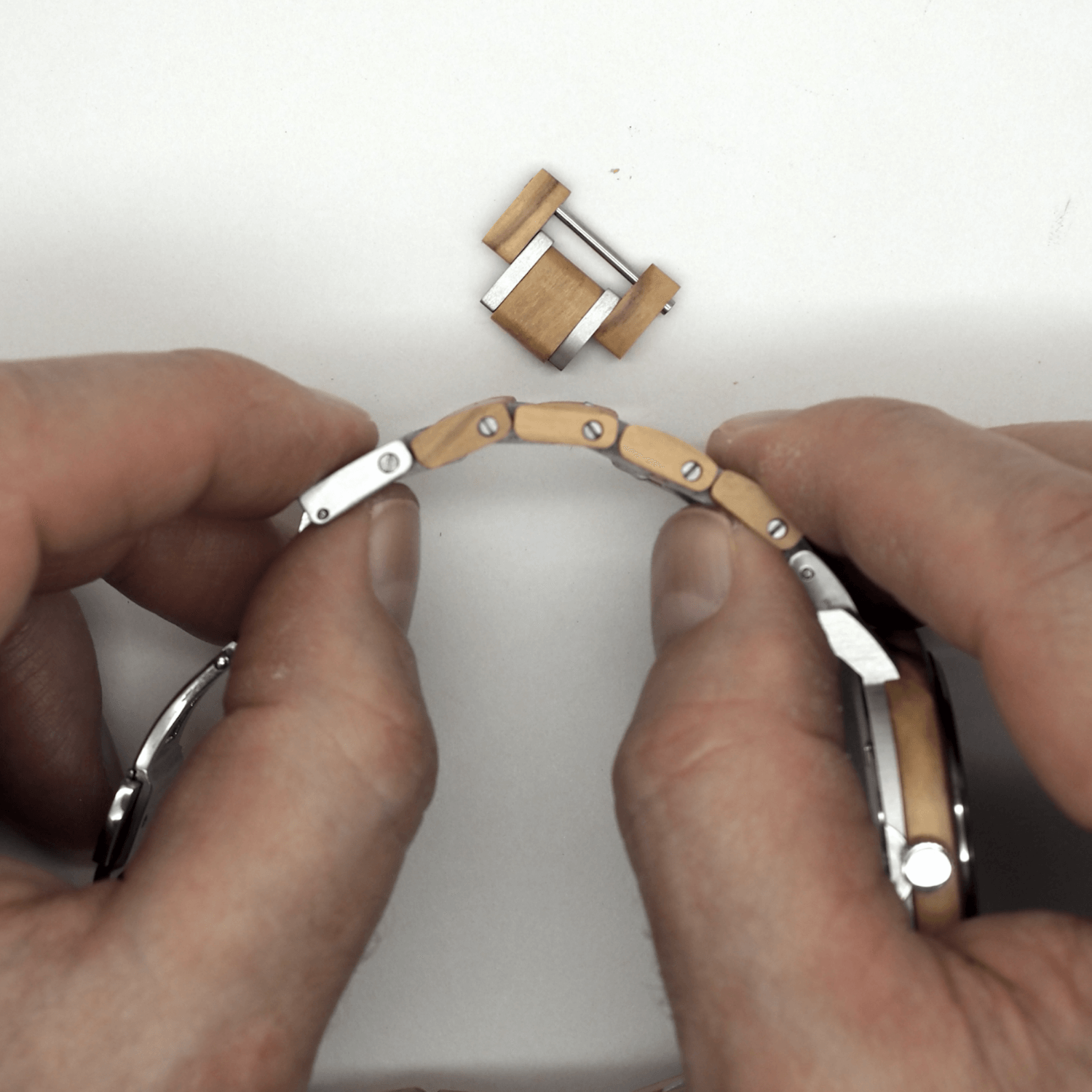 Person holding wooden watch band and link