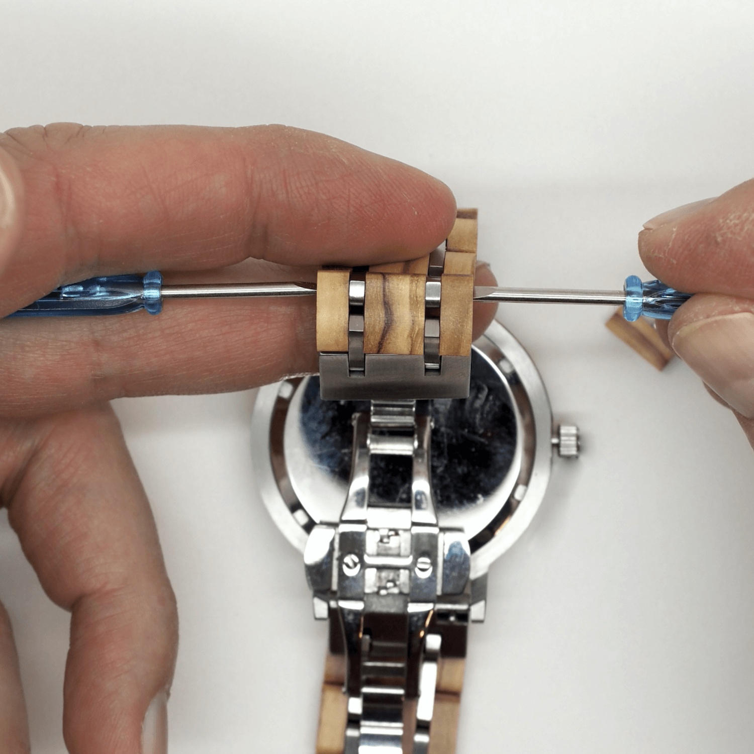 Person holding 2 screwdrivers on wooden watch band
