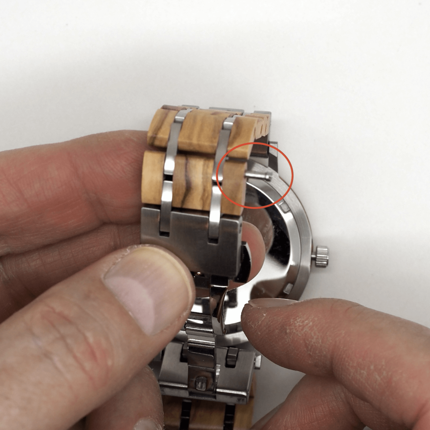 Person pointing to wooden watch band pin