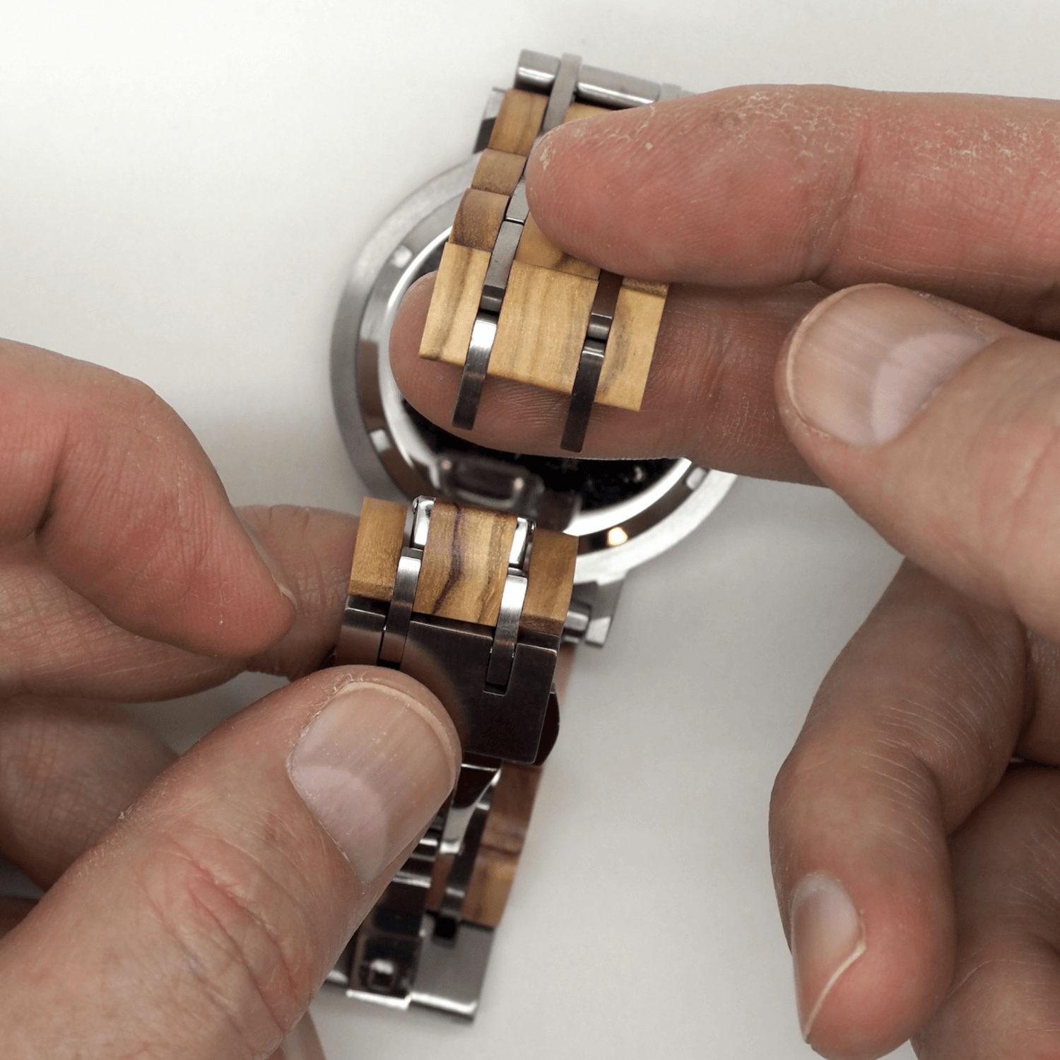 Person holding separated wooden watch band