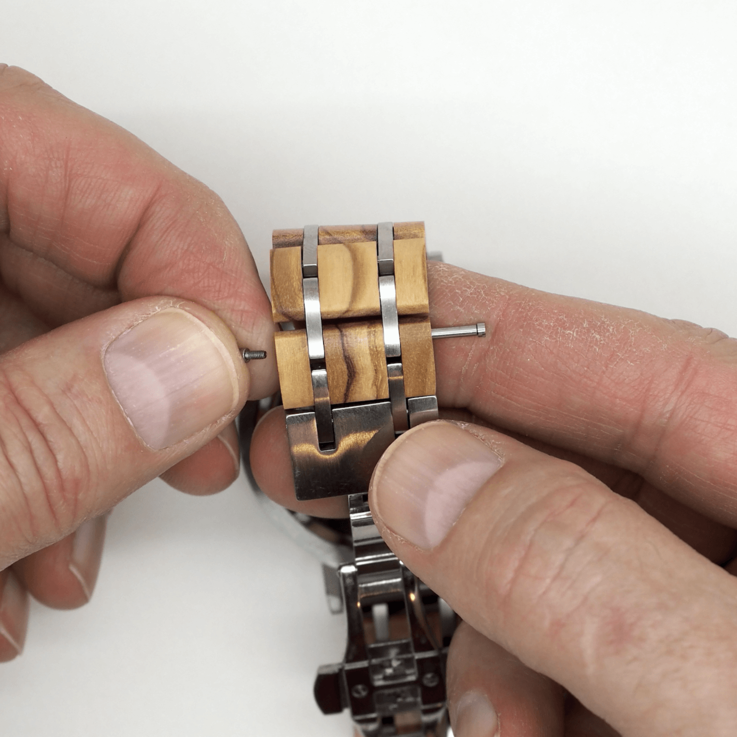 Person holding wooden watch band with screw and pin