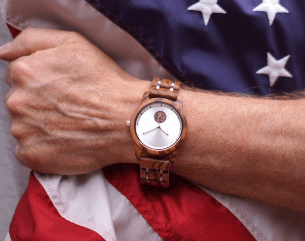 Man holding united states flag with wooden watch