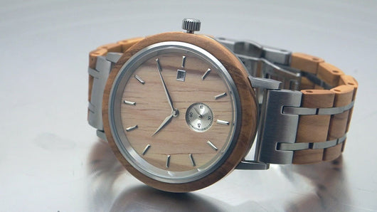 Olive wood and stainless steel watch spinning on turntable