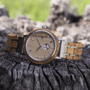 Olive wood and stainless steel watch laying on tree trunk