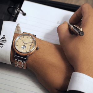 Person wearing wooden and metal watch while writing