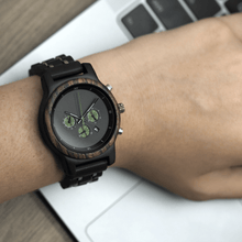 Load image into Gallery viewer, person wearing ebony wooden watch while working on a computer