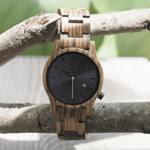 Zebrawood wooden watch hanging off of a tree branch