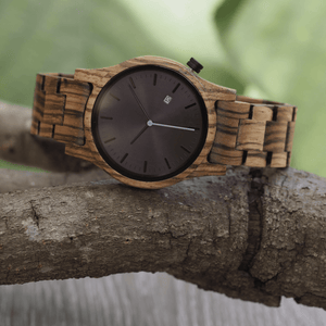 Zebrawood unisex wooden watch with black dial and blue second hand on a branch