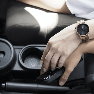 Woman wearing wooden watch in car and holding someone's hand