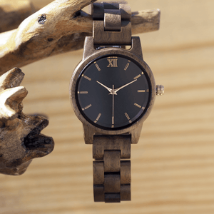 Walnut wooden watch with rose gold accents hanging off of branch