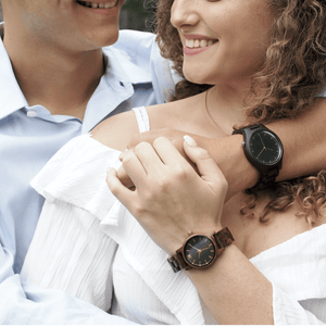 Two people modeling men's and women's wooden watches