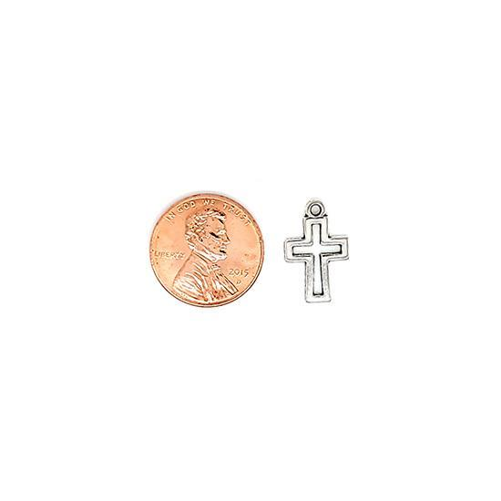 Small cross charm with a penny for scale.