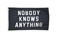 Black outdoor flag. White writing: Nobody Knows Anything