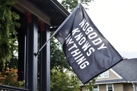 Black flag hanging on porch. White writing: Nobody Knows Anything