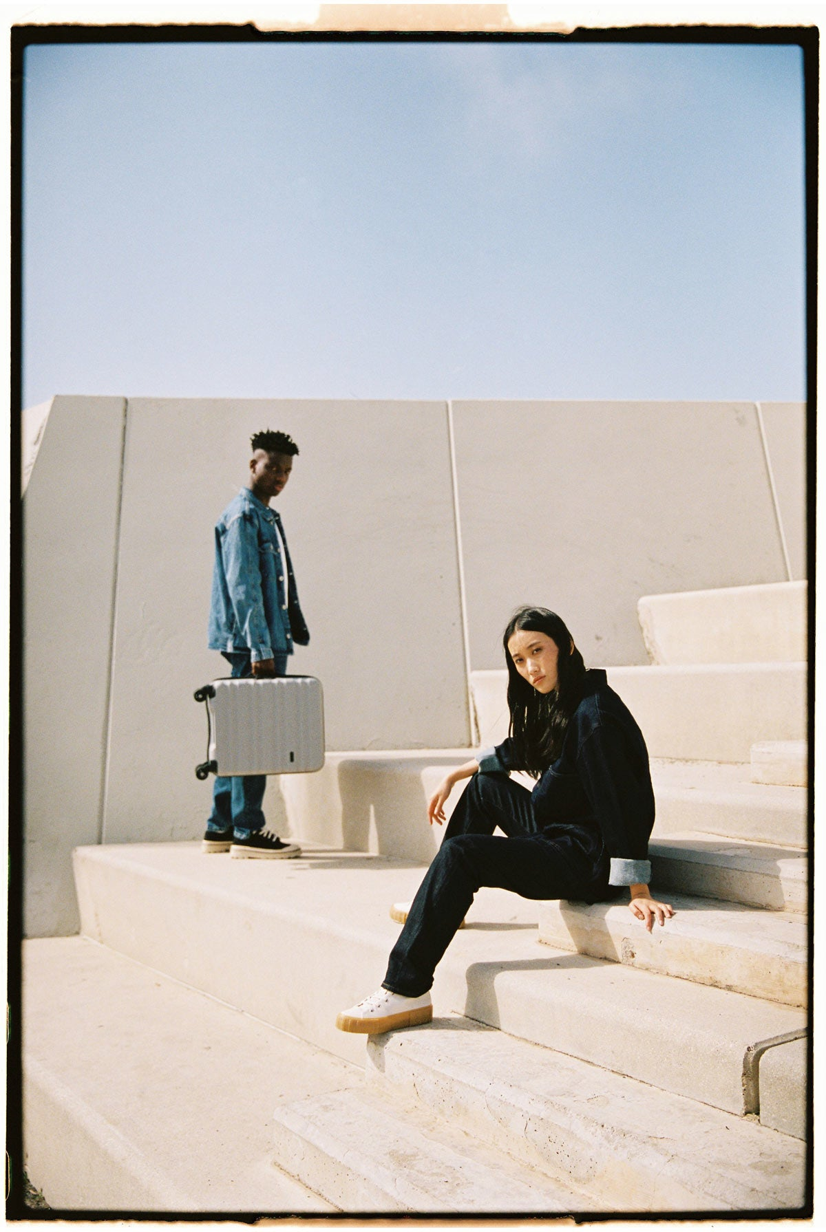Image of Antler Clifton suitcase in grey being held by a male model, with a female model sitting on steps in front