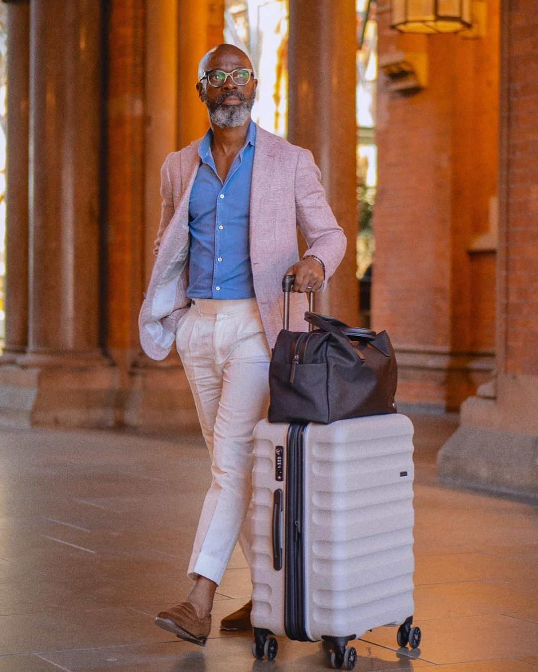 Efe Efetori travels with the Antler Clifton suitcase in taupe and Chelsea overnight bag in black
