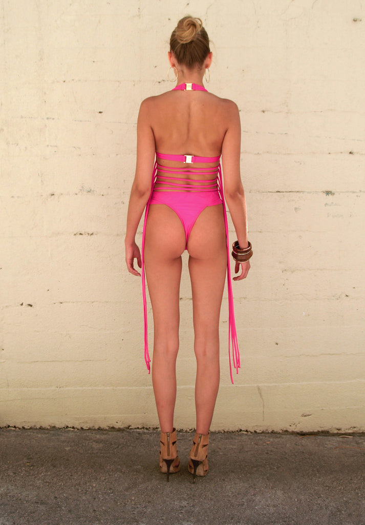 Back View Pink One Piece SwimSuit featuring beautiful strapping detail which can flow free or be crisscrossed around the neck or waist