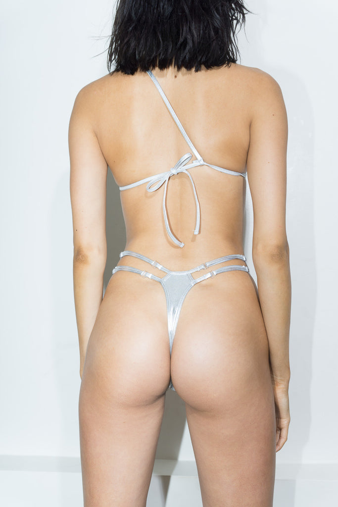 Back View - The Celine is an one should asymmetric metallic silver two piece with a thong strap and adjustable waist straps. As seen on Brooks Nader in SI swimsuit.