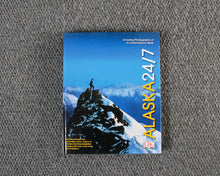 Load image into Gallery viewer, Alaska 24/7 book dust jacket cover featuring a person standing on an Alaskan mountain top