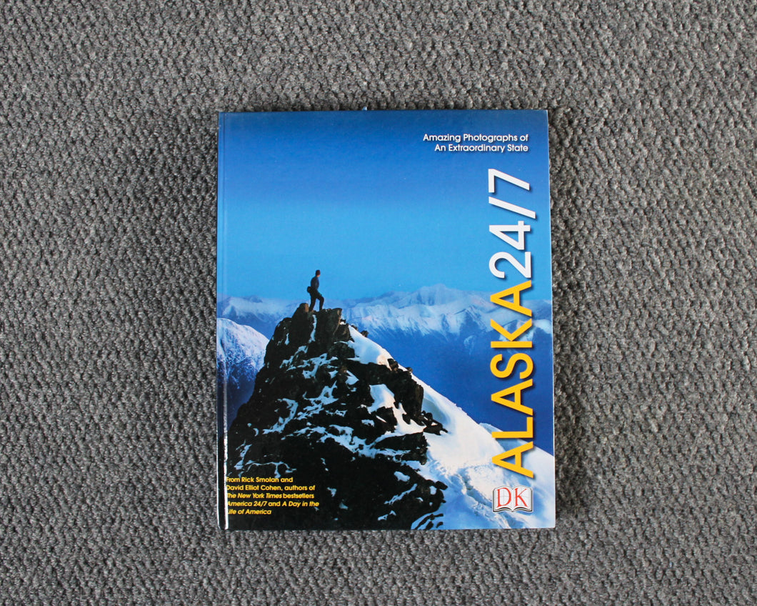 Alaska 24/7 book dust jacket cover featuring a person standing on an Alaskan mountain top