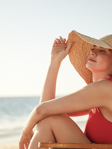 lady on beach with sun hat