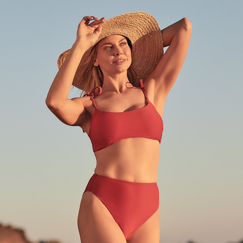 women on beach in red bathing suit with brown hat